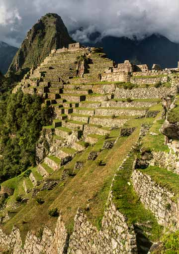 Machu Picchu terraces extend across mountain ridge and down steep mountainside